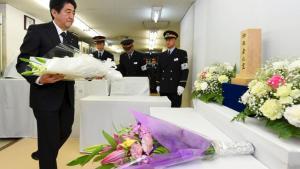 Le Premier ministre japonais Shinzo Abe dépose des fleurs dans le métro, en hommage aux victimes de l'attaque il y a 20 ans. REUTERS/Kyodo