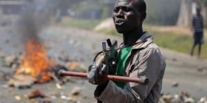 Un manifestant pointe une fausse arme vers des soldats lors d'une manifestation à Bujumbura en juin 2015. © Gildas Ngingo/AP/Sipa