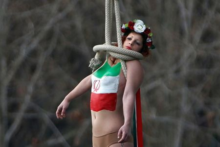 a-topless-activist-of-women-s-rights-group-femen-hangs-from-a-bridge-as-they-stage-a-protest-against-iran-s-president-hassan-rouhani-visit-to-paris-1_55