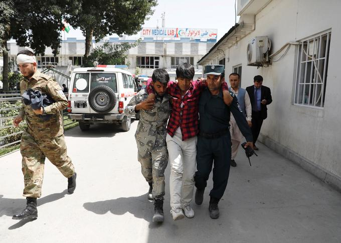 Men carry an injured man to a hospital after a blast in Kabul