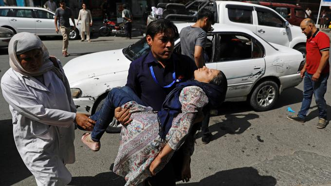A man carries an injured woman to a hospital after a blast in Kabul, Afghanistan